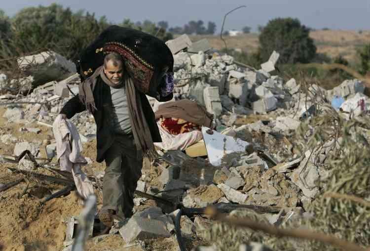 Au lendemain de l'annonce du cessez-le-feu, les Palestiniens commencent tout juste à évaluer le niveau de destruction et de carnage que la bande de Gaza a subi durant 22 jours d'offensive israélienne. Ici, un Gazaoui récupère quelques biens dans les décombres de sa maison.