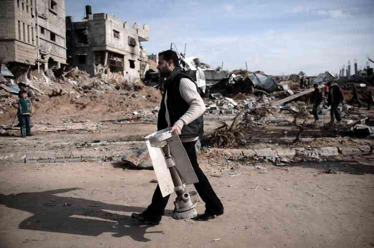 """Dans une rue de Djabalia, un homme porte la queue d'un missie israélien. """"Nous voulons une solution qui garantisse que les chars israéliens ne reviendront pas nous tuer. On parle d'un cessez-le-feu d'une semaine. Je n'ai pas un bon pressentiment. Je doute que ce soit terminé"""", confie à l'agence de presse Reuters Yehya Aziz, un Gazaoui de 28 ans."""