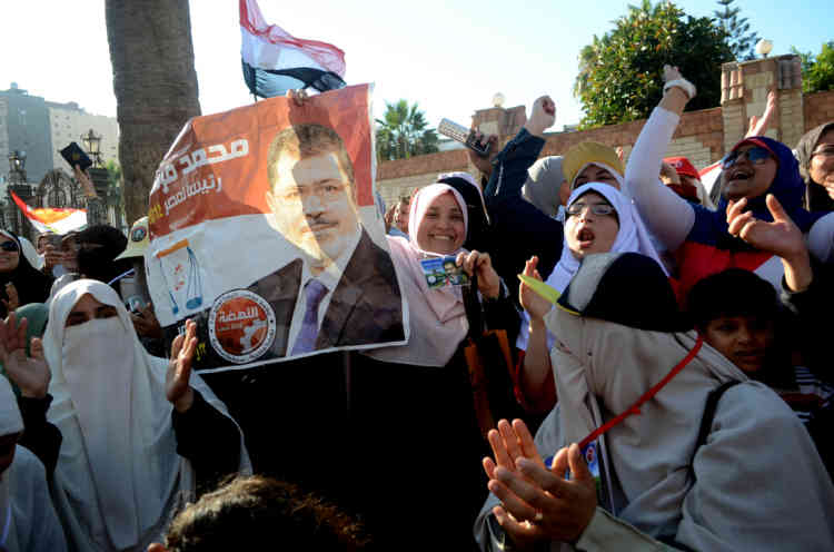 Female supporters of Egypt's Muslim Brotherhood candidate Mohamed Morsi (portrait) celebrate, in the northern coastal city of Alexandria, after Egypt's elections presidential committee declared Morsi as the winner in a divisive run-off with ex-premier Ahmed Shafiq on June 24, 2012. Morsi has vowed to uphold the goals of the revolution that ousted president Hosni Mubarak last year and to share power with other parties. AFP PHOTO / STR