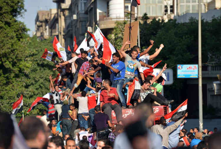 Egyptians holding up their national flag celebrate on June 24, 2012, in Cairo's Tahrir Square, the victory of Muslim Brotherhood member Mohamed Morsi who was declared the first president of Egypt since a popular uprising ousted Hosni Mubarak, capping a tumultuous and divisive military-led transition.  AFP PHOTO / KHALED DESOUKI