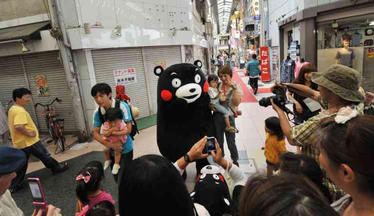 """TO GO WITH STORY Lifestyle-Japan-entertainment-society-business,FEATURE by Miwa Suzuki This photo taken on June 30, 2012 shows the life-size character """"Kumamon"""" posing for visitors at the Yanagase shopping district in Gifu.  A two-day """"grand assembly"""" in the central Japan city of Gifu attracted around 120,000 visitors who were entertained by 47 adult-sized mascots, one from each prefecture, who treated visitors to songs, dances and endless photo opportunities.   AFP PHOTO / KAZUHIRO NOGI"""