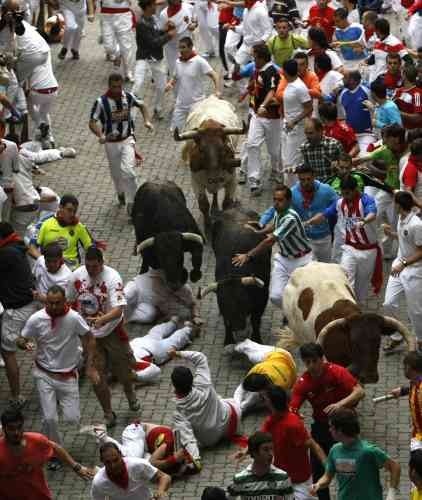 Runners fall in front of Fuente Ymbro fighting bulls at the entrance to the bullring during the fifth running of the bulls at the San Fermin festival in Pamplona July 11, 2012. Several runners suffered light injuries in a run that lasted three minutes and twelve seconds, according to local media. REUTERS/Joseba Etxaburu (SPAIN - Tags: ANIMALS SOCIETY)