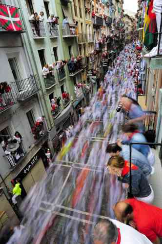 Revelers run on Estafeta street beside to Fuente Ymbro fighting bulls ranch as people look on from balconies above, during the fifth running of the bulls, at the San Fermin fiestas, in Pamplona, northern Spain, Wednesday, July 11, 2012. (AP Photo/Alvaro Barrientos)