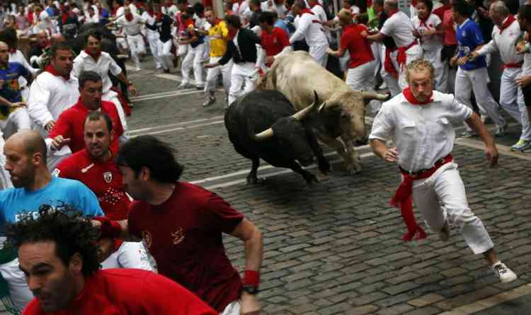Runners sprint alongside Fuente Ymbro fighting bulls at the Estafeta corner during the fifth running of the bulls of the San Fermin festival in Pamplona July 11, 2012. Several runners suffered light injuries in a run that lasted three minutes and twelve seconds, according to local media. REUTERS/Susana Vera (SPAIN - Tags: SOCIETY ANIMALS)