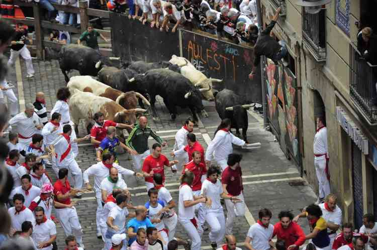Revelers run in front to pack of Fuente Ymbro ranch fighting bulls on Estafeta street, during the fifth running of the bulls, at the San Fermin fiestas, in Pamplona northern Spain, Wednesday, July 11, 2012. (AP Photo/Alvaro Barrientos)