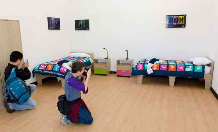 Members of the media take pictures of a mock-up of a typical athletes room inside the London 2012 Olympic Athletes Village in east London, on July 12, 2012. The 2012 Olympic games will begin on July 27, 2012. AFP PHOTO/LEON NEAL