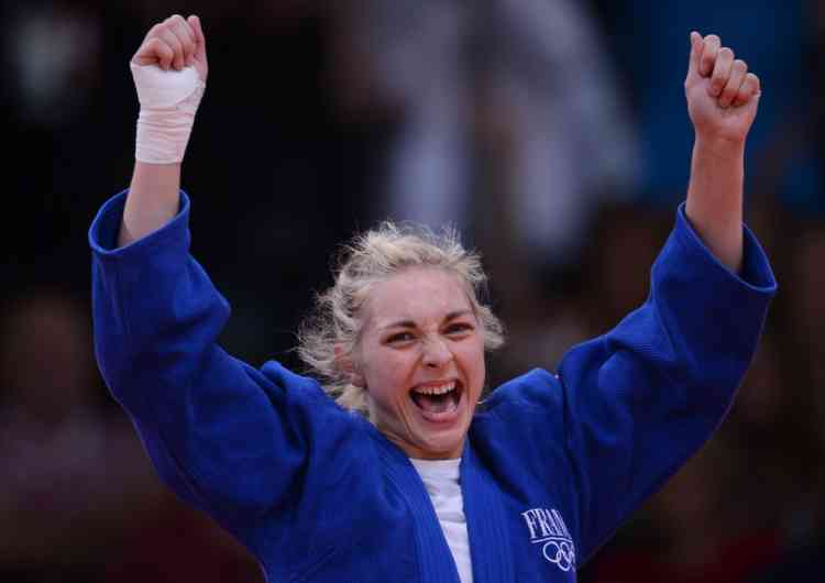 France's Automne Pavia celebrates with her coach after winning against Hungary's Hedvig Karakas during their women's -57kg judo contest bronze medal match of the London 2012 Olympic Games on July 30, 2012 ExCel arena in London.    AFP PHOTO / FRANCK FIFE