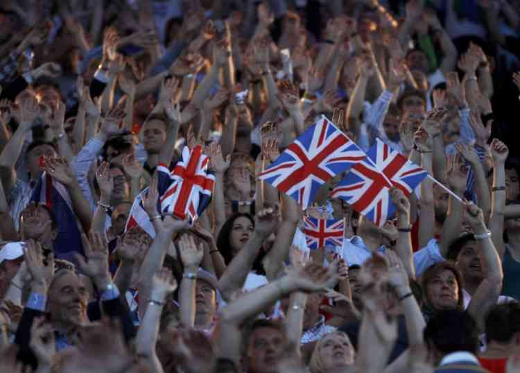 Guests stand and wave Britain's flag during the closing ceremony of the London 2012 Olympic Games at the Olympic Stadium August 12, 2012.          REUTERS/Gary Hershorn (BRITAIN  - Tags: SPORT OLYMPICS)
