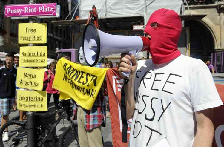 A masked activist of of the human rights organization Amnesty International shouts slogans next to the pasted street sign of the Marienplatz place with Pussy-Riot-Platz (Platz is German for place) in Munich, southern Germany, Friday, Aug. 17, 2012, during a demonstration for the Russian punk band Pussy Riot. Three members of Russian punk group Pussy Riot were jailed in March and charged with hooliganism motivated by religious hatred after their punk performance against President Putin in Moscow's main cathedral. A judge found three members of the provocative punk band Pussy Riot guilty of hooliganism on Friday, in a case that has drawn widespread international condemnation as an emblem of Russia's intolerance of dissent. (AP Photo/dapd, Lennart Preiss)