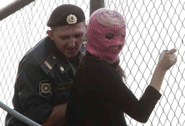 """A policeman detains a supporter of the female punk band """"Pussy Riot"""" while climbing a fence enclosing the Turkish embassy near a court building in Moscow, August 17, 2012. A judge sentenced three women who staged an anti-Kremlin protest on the altar of Moscow's main Russian Orthodox church to two years in jail on Friday in a trial seen as test of President Vladimir Putin's tolerance of dissent.   REUTERS/Sergei Karpukhin (RUSSIA - Tags: CRIME LAW POLITICS CIVIL UNREST)"""