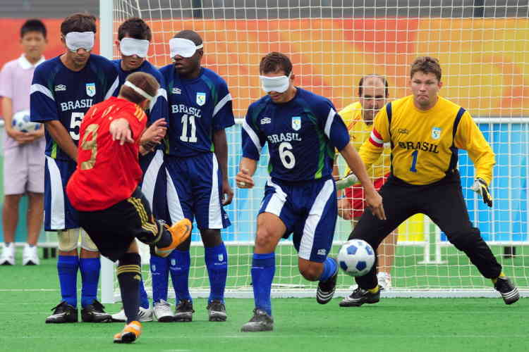 Jesus Antonio Martin (#9) of Spain shoots from a free-kick against a Brazil wall of Damiao Ramos (L#5), Ricardo Alves (2/L), Jefferson Goncalves (3/L#11), Marcos Felipe (4/L#6) and goalkeeper Fabio Vasconcelos Ribiero (R#1) in their men's 5-a-side football match during the 2008 Beijing Paralympic Games on September 9, 2008 at the Olympic Green hockey field in Beijing.  Brazil defeated Spain 1-0 in a sport where each team fields four blind players and one sighted or visually impaired goalkeeper.    AFP PHOTO / Frederic J. BROWN