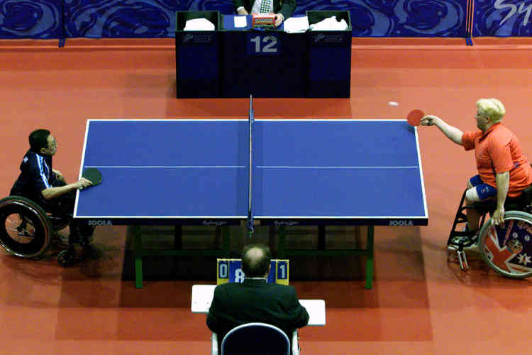 Paralympic athletes Scott Robertson (R) from Great Britain returns a shot to Japan's Toshihiko Oka during their Class Five Mens Singles Table Tennis match at the eleventh Paralympic Games in Sydney October 24, 2000. Oka won the match 20-22, 22-19, 22-19. More than 300 players competed in the preliminary rounds today, with the finals being played tomorrow. More than 4000 disabled athletes from 125 countries are competing in 18 sports at the eleventh Paralympic Games.