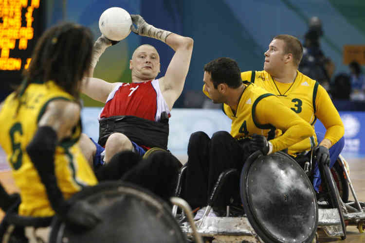 Britain's Jason Roberts passes the ball as Australia's Ryley Batt (3), Cameron Carr (4) and Scott Vitale (6) guard during their mixed wheelchair rugby preliminaries at the Beijing 2008 Paralympic Games September 14, 2008.       REUTERS/Claro Cortes IV    (CHINA)