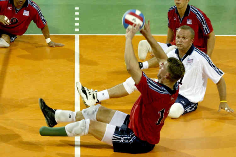 U.S. players watch team mate Rasmussen volley the ball during Athens 2004 Paralympics sitting volleyball match against Greece.  U.S. players watch team mate Brent Rasmussen (front) volley the ball during a preliminary round sitting volleyball match against Greece during Athens 2004 Paralympic Games at Helliniko complex in Greece September 22, 2004. U.S.won 3-1. REUTERS/Yiorgos Karahalis