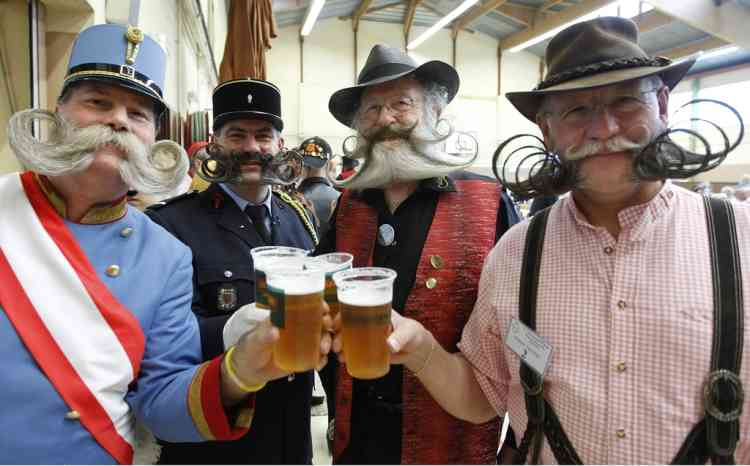Participants have a beer as they take part in the 2012 European Beard and Moustache Championships in Wittersdorf near Mulhouse, Eastern France, September 22, 2012. More than a hundred participants competed in the first European Beard and Moustache Championships organized in France. REUTERS/Vincent Kessler (FRANCE - Tags: SOCIETY)