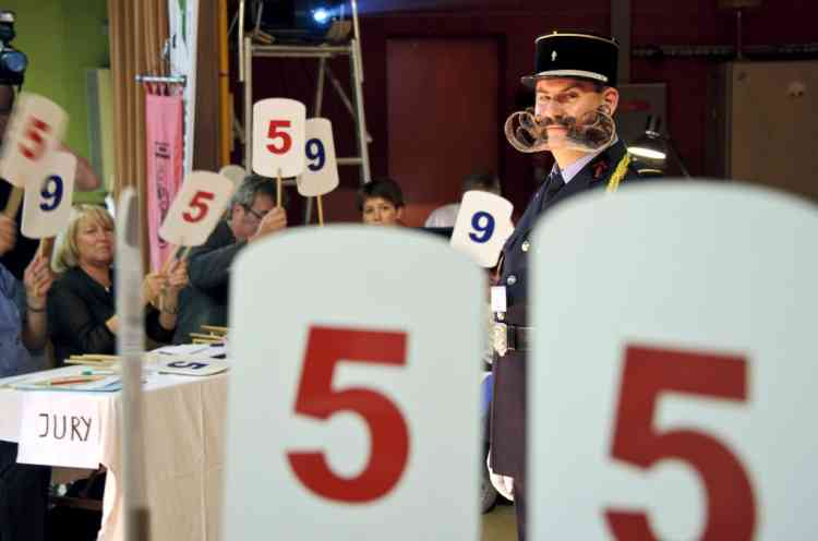 Jury members vote as a competitor stands on stage during the first edition of the European Beard and Moustache championships on September 22, 2012 in Wittersdorf, eastern France.  AFP PHOTO / SEBASTIEN BOZON
