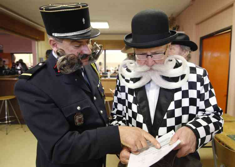 Participants read documents as they take part in the 2012 European Beard and Moustache Championships in Wittersdorf near Mulhouse, Eastern France, September 22, 2012. More than a hundred participants competed in the first European Beard and Moustache Championships organized in France. REUTERS/Vincent Kessler (FRANCE - Tags: SOCIETY)