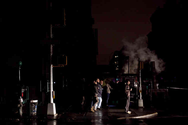 NEW YORK, NY - OCTOBER 29: People are illuminated in the headlights of a taxi during the power outage on October 29, 2012 in Manhattan, New York. Hurricane Sandy, which threatens 50 million people in the Mid-Atlantic area of the United States, is expected to bring days of rain, high winds and possibly heavy snow. New York Governor Andrew Cuomo announced the closure of all New York City bus, subway and commuter rail services as of Sunday evening.   Allison Joyce/Getty Images/AFP== FOR NEWSPAPERS, INTERNET, TELCOS & TELEVISION USE ONLY ==