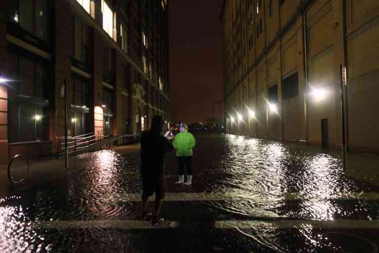 NEW YORK, NY - OCTOBER 29: People take photographs in flood water in the Meatpacking District on October 29, 2012 in Manhattan, New York. Hurricane Sandy, which threatens 50 million people in the Mid-Atlantic area of the United States, is expected to bring days of rain, high winds and possibly heavy snow. New York Governor Andrew Cuomo announced the closure of all New York City bus, subway and commuter rail services as of Sunday evening.   Allison Joyce/Getty Images/AFP== FOR NEWSPAPERS, INTERNET, TELCOS & TELEVISION USE ONLY ==