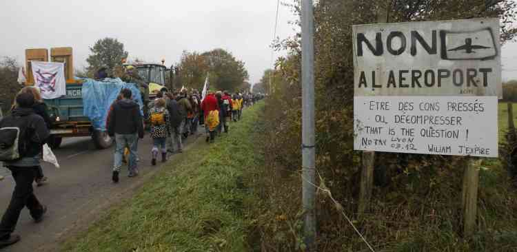 "People walk near a sign which reads, ""Airport No"" as they take part in a demonstration against plans to construct a new airport in Notre-Dame-des-Landes, western France, November 17, 2012. The new airport, some 30kms (19 miles) from Nantes, is scheduled to be constructed for 2017.  REUTERS/Stephane Mahe (FRANCE  - Tags: TRANSPORT CIVIL UNREST POLITICS)"