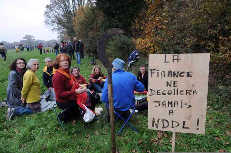 "Farmers, environmental activists and opponents take part in a demonstration against a project to build an international airport, next to a placard reading ""Finance shall not take off at Notre-Dame-des-Landes"", on November 17, 2012 in Notre-Dame-des-Landes, western France. The project was signed in 2010 and the international airport is supposed to open in 2017 near the city of Nantes.   AFP PHOTO/JEAN-FRANCOIS MONIER"