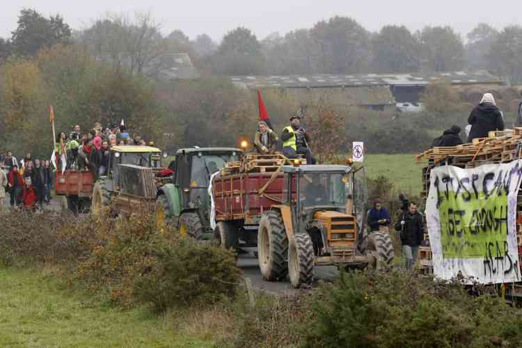People ride on tractors as they take part in a demonstration against plans to construct a new airport in Notre-Dame-des-Landes, western France, November 17, 2012. The new airport, some 30kms (19 miles) from Nantes, is scheduled to be constructed for 2017.  REUTERS/Stephane Mahe (FRANCE  - Tags: TRANSPORT CIVIL UNREST POLITICS)