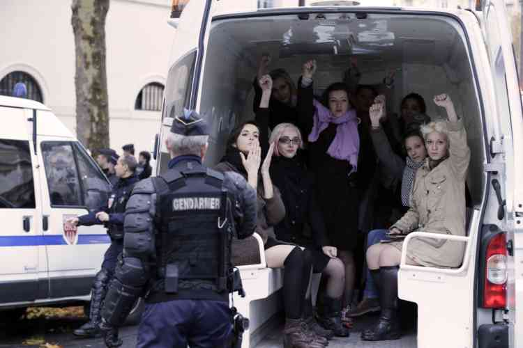 Topless activists of the Ukrainian women movement Femen raise fist in a van after an action against the fierce opposition from the Roman Catholic Church to authorise gay marriage on November 18, 2012 in Paris.   AFP PHOTO KENZO TRIBOUILLARD