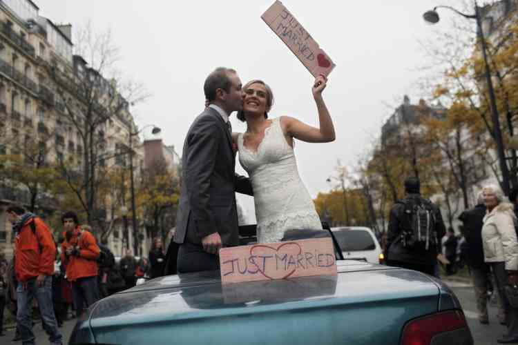 """A bride and a groom stand in a car as they protest against French President Francois Hollande's plan to legalize marriage and adoption for gay people, in Paris, Saturday Nov. 17, 2012. Saturday's event, entitled """"march for everyone"""", attracted several thousand people in cities such as Lyon, Marseille and Paris.  (AP Photo/Thibault Camus)"""