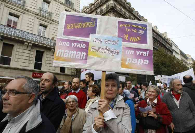 """A woman holds a placard reading"""" A real mother, a real father, a true marriage"""", during a demonstration,  against the government project to legalize same sex marriage and adoption for same-sex couples, in Marseille, southern France, Saturday, Nov. 17, 2012. (AP Photo/Claude Paris)"""