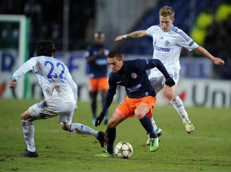 Montpellier's French forward Anthony Mounier (C) vies with Schalke's Japanese defender Atsuto Uchida (L) and Schalke's Romanian forward Ciprian Marica (R)  during the UEFA Champions League match Montpellier vs. Schalke on December 4, 2012 at the La Mosson stadium in Montpellier.  AFP PHOTO / PASCAL GUYOT
