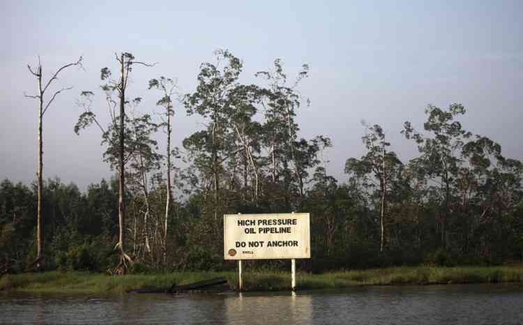 A warning sign belonging to the company Royal Dutch Shell is seen along the Nembe creek in Nigeria's oil state of Bayelsa December 2, 2012. Thousands of people in Nigeria engage in a practice known locally as 'oil bunkering' - hacking into pipelines to steal crude then refining it or selling it abroad. The practice, which leaves oil spewing from pipelines for miles around, managed to lift around a fifth of Nigeria's two million barrel a day production last year according to the finance ministry. Picture taken December 2, 2012. REUTERS/Akintunde Akinleye    (NIGERIA - Tags: BUSINESS ENVIRONMENT SOCIETY INDUSTRIAL ENERGY) ATTENTION EDITORS - PICTURE 28 OF 28 FOR PACKAGE 'NIGERIA'S ILLEGAL OIL BUNKERERS'. SEARCH 'OIL BUNKERING' FOR ALL IMAGES