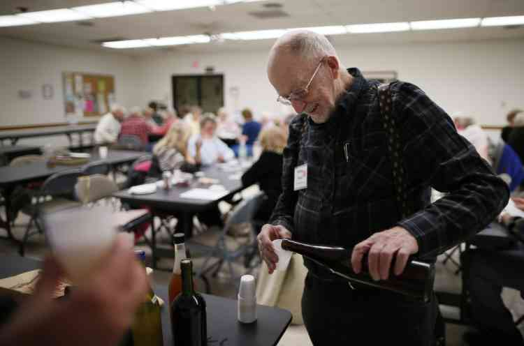 Whitey Sauer, 84, shares out his homemade wine at a singles club in Sun City, Arizona, January 4, 2013. Sun City was built in 1959 by entrepreneur Del Webb as America's first active retirement community for the over-55's. Del Webb predicted that retirees would flock to a community where they were given more than just a house with a rocking chair in which to sit and wait to die. Today's residents keep their minds and bodies active by socializing at over 120 clubs with activities such as square dancing, ceramics, roller skating, computers, cheerleading, racquetball and yoga. There are 38,500 residents in the community with an average age 72.4 years. Picture taken January 4, 2013.    REUTERS/Lucy Nicholson (UNITED STATES - Tags: SOCIETY)