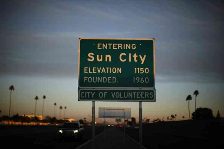 A sign marks the boundary of Sun City, Arizona, January 6, 2013. Sun City was built in 1959 by entrepreneur Del Webb as America's first active retirement community for the over-55's. Del Webb predicted that retirees would flock to a community where they were given more than just a house with a rocking chair in which to sit and wait to die. Today's residents keep their minds and bodies active by socializing at over 120 clubs with activities such as square dancing, ceramics, roller skating, computers, cheerleading, racquetball and yoga. There are 38,500 residents in the community with an average age 72.4 years. Picture taken January 6, 2013.  REUTERS/Lucy Nicholson (UNITED STATES - Tags: SOCIETY)
