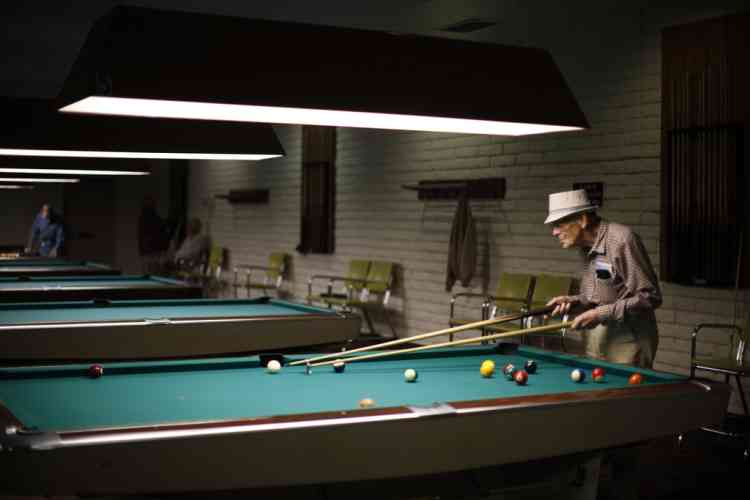 Curtis Hay, 82, who worked for Boeing for 30 years, plays pool in Sun City, Arizona, January 5, 2013. Sun City was built in 1959 by entrepreneur Del Webb as America's first active retirement community for the over-55's. Del Webb predicted that retirees would flock to a community where they were given more than just a house with a rocking chair in which to sit and wait to die. Today's residents keep their minds and bodies active by socializing at over 120 clubs with activities such as square dancing, ceramics, roller skating, computers, cheerleading, racquetball and yoga. There are 38,500 residents in the community with an average age 72.4 years. Picture taken January 5, 2013.  REUTERS/Lucy Nicholson (UNITED STATES - Tags: SOCIETY)
