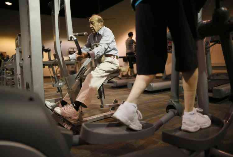 Dario Rossini, 90, (L) works out at a recreation center in Sun City, Arizona, January 5, 2013. Rossini said he does at least 100 sit-ups a day, and works out at the gym 4-5 days a week to maintain healthy muscles and bones. Sun City was built in 1959 by entrepreneur Del Webb as America's first active retirement community for the over-55's. Del Webb predicted that retirees would flock to a community where they were given more than just a house with a rocking chair in which to sit and wait to die. Today's residents keep their minds and bodies active by socializing at over 120 clubs with activities such as square dancing, ceramics, roller skating, computers, cheerleading, racquetball and yoga. There are 38,500 residents in the community with an average age 72.4 years. Picture taken January 5, 2013.                REUTERS/Lucy Nicholson (UNITED STATES - Tags: SOCIETY TPX IMAGES OF THE DAY)