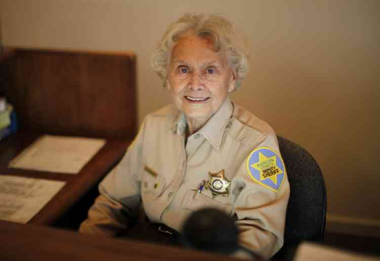 Sun City Sheriff's Posse member Elizabeth Neubauer, 90, sits at the reception desk in Sun City, Arizona, January 7, 2013. Sun City was built in 1959 by entrepreneur Del Webb as America's first active retirement community for the over-55's. Del Webb predicted that retirees would flock to a community where they were given more than just a house with a rocking chair in which to sit and wait to die. Today's residents keep their minds and bodies active by socializing at over 120 clubs with activities such as square dancing, ceramics, roller skating, computers, cheerleading, racquetball and yoga. There are 38,500 residents in the community with an average age 72.4 years.    Picture taken January 7, 2013. REUTERS/Lucy Nicholson (UNITED STATES - Tags: SOCIETY)