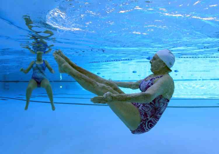 Inge Natoli, 90, (R) who emigrated to Michigan from Germany and has lived in Sun City for 29 years practices synchronized swimming with Barbara Miller, 77, in Sun City, Arizona, January 9, 2013. Sun City was built in 1959 by entrepreneur Del Webb as America's first active retirement community for the over-55's. Del Webb predicted that retirees would flock to a community where they were given more than just a house with a rocking chair in which to sit and wait to die. Today's residents keep their minds and bodies active by socializing at over 120 clubs with activities such as square dancing, ceramics, roller skating, computers, cheerleading, racquetball and yoga. There are 38,500 residents in the community with an average age 72.4 years. Picture taken January 9, 2013.  REUTERS/Lucy Nicholson (UNITED STATES - Tags: SOCIETY)