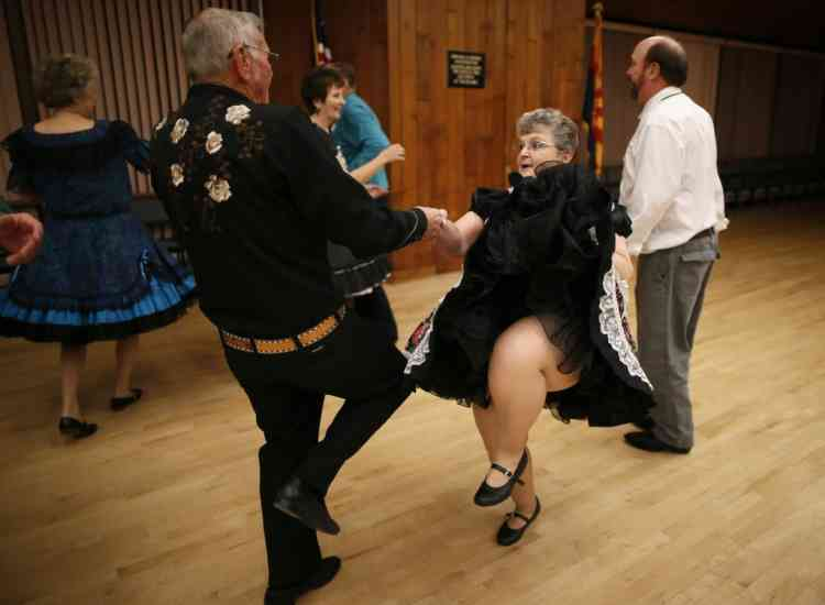 Robert Harker, 73, and his wife Nancy, 70, square dance in Sun City, Arizona, January 8, 2013. Sun City was built in 1959 by entrepreneur Del Webb as America's first active retirement community for the over-55's. Del Webb predicted that retirees would flock to a community where they were given more than just a house with a rocking chair in which to sit and wait to die. Today's residents keep their minds and bodies active by socializing at over 120 clubs with activities such as square dancing, ceramics, roller skating, computers, cheerleading, racquetball and yoga. There are 38,500 residents in the community with an average age 72.4 years.    Picture taken January 8, 2013.  REUTERS/Lucy Nicholson (UNITED STATES - Tags: SOCIETY)