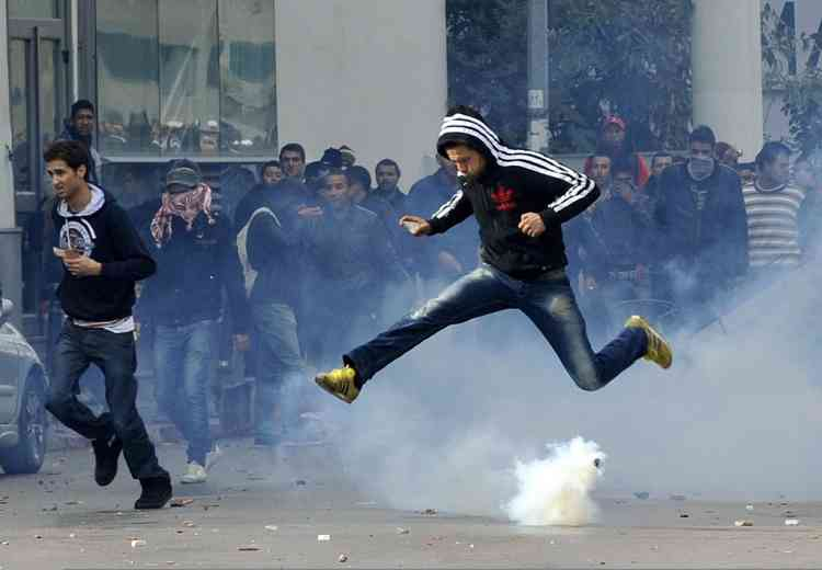 A Tunisian protester jumps amid smoke after police fired tear gas during a rallye outside the Interior ministry to protest after Tunisian opposition leader and outspoken government critic Chokri Belaid was shot dead with three bullets fired from close range, on February 6, 2013 in Tunis. The protesters, who massed on Habib Bourguiba Avenue, epicentre of the 2011 uprising that ousted ex-dictator Zine El Abidine Ben Ali, pelted the police with bottles and the police responded by firing tear gas, chasing the protesters and beating them with batons. AFP PHOTO / FETHI BELAID