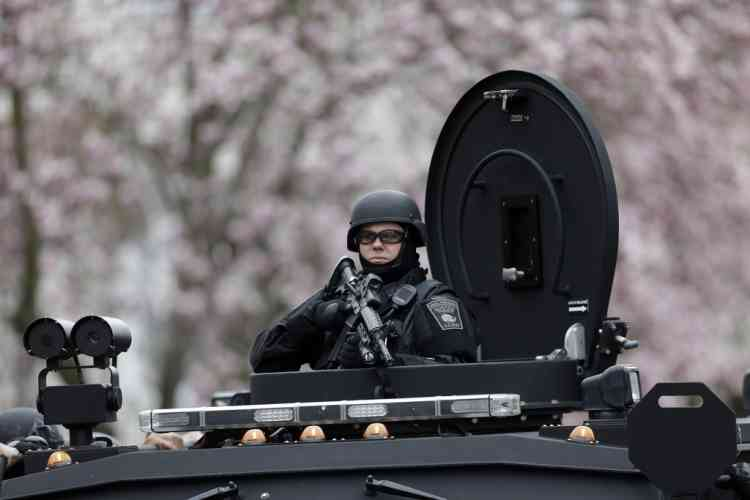 A police officer in tactical gear conducts a search for a suspect in the Boston Marathon bombings, Friday, April 19, 2013, in Watertown, Mass. The bombs that blew up seconds apart near the finish line of the Boston Marathon left the streets spattered with blood and glass, and gaping questions of who chose to attack and why. (AP Photo/Matt Rourke)