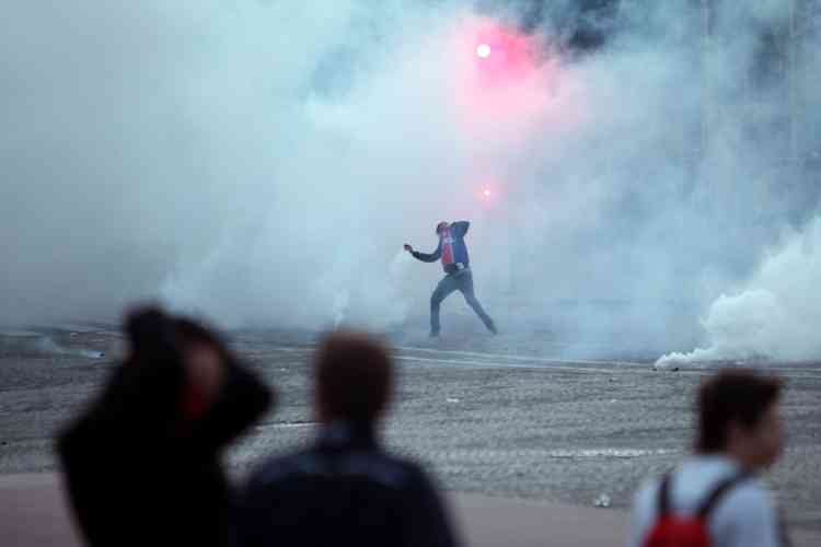 A Paris Saint Germain supporter throws a gas canister back to riot police officers during clashes after the celebration of PSG's French League title, in Paris, Monday, May 13, 2013. Paris Saint-Germain clinched its first French league title since 1994 by defeating Lyon 1-0 on Sunday. PSG has now an unassailable seven-point lead at the top of the standings. With just two rounds left, second-place Marseille can no longer catch its fierce rival. (AP Photo/Thibault Camus)