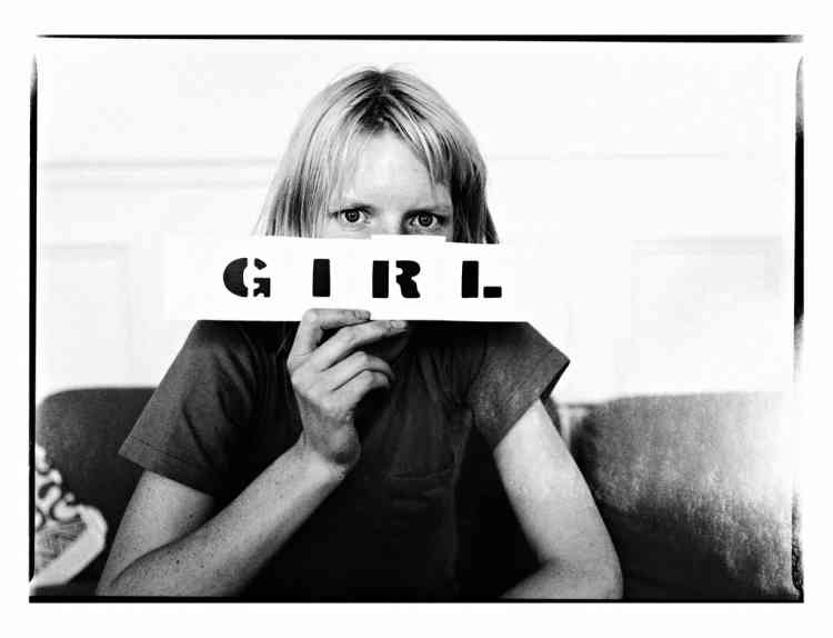 """""""J'ai réalisé, il y a un certain temps, que j'avais pris tellement de photos de filles allongées ou assises sur l'herbe que je pourrais faire un livre qui s'intitulerait Des filles sur l'herbe. J'y travaille toujours. Quand j'ai commencé à le concevoir, j'ai choisi une police de  caractères pour la couverture et j'ai découpé les quatre mots pour essayer différentes dispositions. Un jour, Kirsten Owen est venue prendre une tasse de thé et a vu le mot """"fille"""" sur ma table de travail. Elle a dit : """"Je suis une fille"""" et a tenu le papier avec le mot devant  son visage. Encore une photo qui s'est faite toute seule. L'important, c'est d'être toujours prêt pour ces moments imprévus."""" -"""