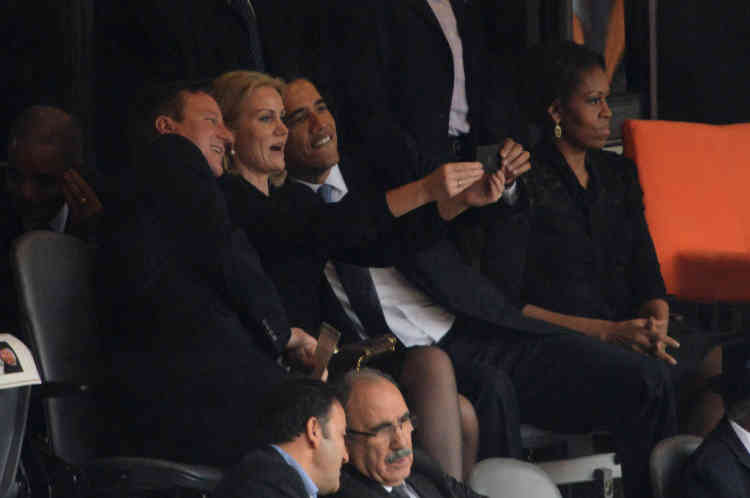 US President  Barack Obama (R) and British Prime Minister David Cameron pose for a picture with Denmark's Prime Minister Helle Thorning Schmidt (C) next to US First Lady Michelle Obama (R) during the memorial service of South African former president Nelson Mandela at the FNB Stadium (Soccer City) in Johannesburg on December 10, 2013. Mandela, the revered icon of the anti-apartheid struggle in South Africa and one of the towering political figures of the 20th century, died in Johannesburg on December 5 at age 95.   AFP PHOTO / ROBERTO SCHMIDT