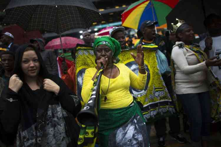 A woman plays a vuvuzela while others sing and dance at a mass memorial for late former South African President Nelson Mandela at the First National Bank Stadium in Johannesburg December 10, 2013. World leaders, from U.S. President Barack Obama to Cuba's Raul Castro, will pay homage to Mandela at the memorial that will recall his gift for bringing enemies together across political and racial divides.REUTERS/Ronen Zvulun (SOUTH AFRICA - Tags: POLITICS OBITUARY)