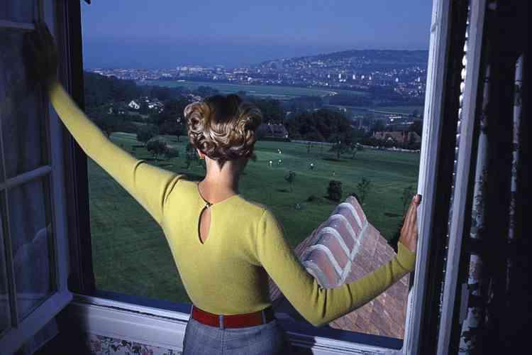 """""""Les gens disent parfois que mes photographies leur font penser  à une scène sortie tout droit d'un film d'Alfred Hitchcock. Peut-être est-ce parce que j'ai une certaine vision anglaise des choses ?  J'ai toujours aimé les images d'Hitchcock. Elles sont très factuelles, presque banales, cela crée une ambiance beaucoup  plus étrange que ne le feraient des effets spéciaux. Et c'est tout à fait ça ici. Juste une fille qui regarde par la fenêtre. Ce qui est étrange, c'est la vue. Cela me rappelle une sorte de """"passé récent"""", mais pas vraiment réel. Cette photographie a été prise pour Marie Claire  dans les années 1980. Une vue sur Deauville. Avec au fond,  de l'autre côté de la mer, l'Angleterre."""""""