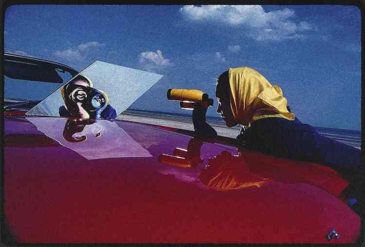 """""""C'était une publicité pour un nouveau film Kodak, capable de restituer des couleurs plus vives et lumineuses. Nous l'avons shootée  à Deauville, lors d'un jour typiquement venteux. Mon idée première était de montrer une fille se regardant dans un miroir à travers  une paire de jumelles. Je voulais un miroir avec une forme bizarre, mais on a finalement décidé de juste dérouler une feuille  de plastique réfléchissant sur un cadre en bois. Mais sur une plage pleine de vent ?... L'effet ne cessait de changer sous la brise.  J'ai plusieurs versions de cette photo, chacune avec une distorsion différente. Imprévisible mais fantastique.  Merci à ce jour venteux, car c'est un bien meilleur cliché que celui que j'avais prévu au départ."""" -"""