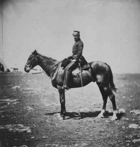 Captain Clifford, in uniform, astride a horse, facing front.