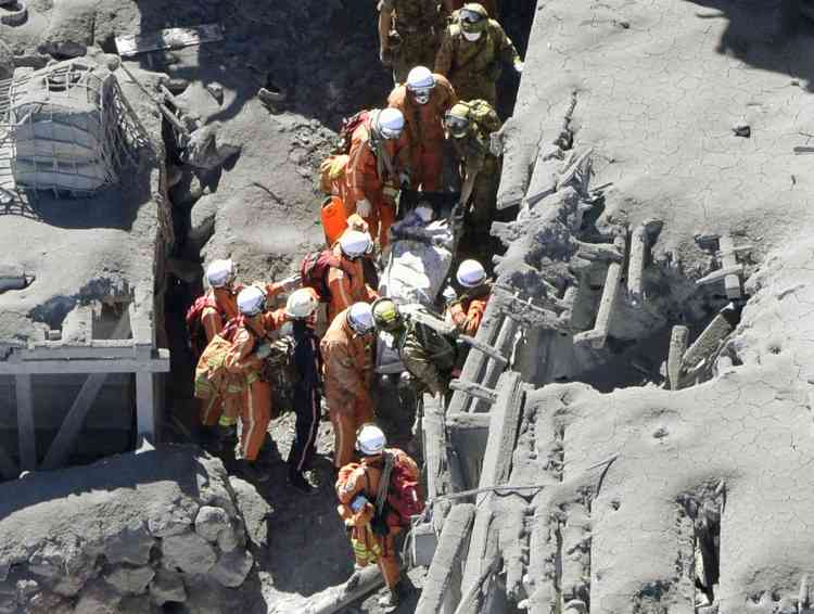 Japan Self-Defense Force (JSDF) soldiers and firefighters carry an injured person among mountain lodges, covered with volcanic ash, near a crater of Mt. Ontake, which straddles Nagano and Gifu prefectures in this September 28, 2014 photo taken and released by Kyodo. More than 500 Japanese military and police set out on Sunday to search the peak of a volcano popular with hikers a day after its sudden eruption trapped hundreds on the mountain for hours, amid conflicting reports about missing and injured climbers.   Mandatory credit.   REUTERS/Kyodo (JAPAN - Tags: DISASTER ENVIRONMENT SOCIETY) 