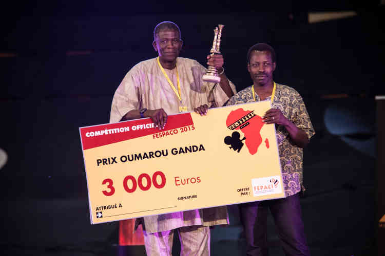 Le réalisateur burkinabé Sekou Traoré reçoit le prix «Oumarou Ganda» de la première œuvre pour son film «L'Œil du cyclone», des mains du cinéaste malien Cheick Oumar Sissoko.