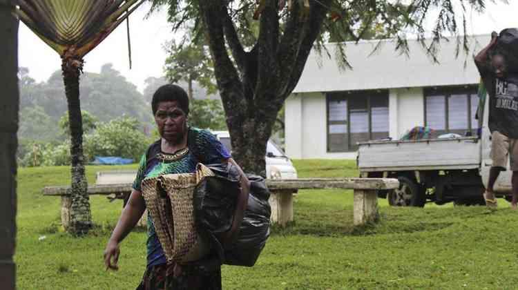 Des habitants de Port Vila, la capitale de l'archipel située sur l'île d'Éfaté, emportent leurs affaires pour les mettre à l'abri.